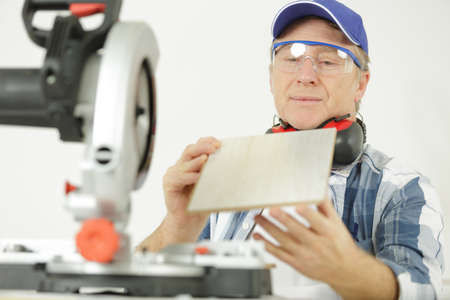 mature man assessing wood he has prepared with circular saw Stockfoto