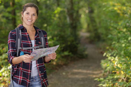 smiling healthy woman hiker holding map