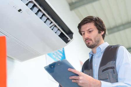 cooler technician doing maintenance check-up Фото со стока