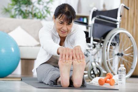 a senior woman stretching leg
