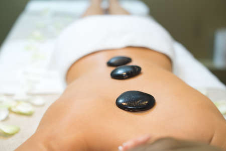 hot stones placed along womans back