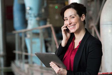femme tenant une tablette électronique dans un grand entrepôt Banque d'images
