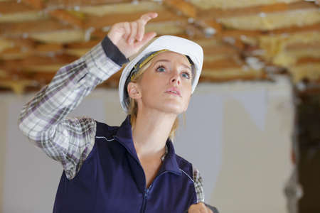 young woman engineer or contractor pointing upward in renovation property Stok Fotoğraf