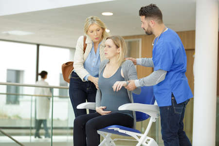 a pregnant woman in pain sitting on a wheelchair
