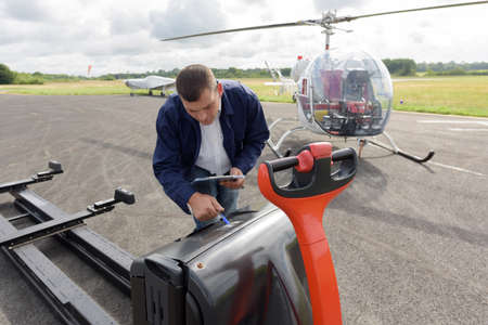 a man charging firemans helicopter Imagens