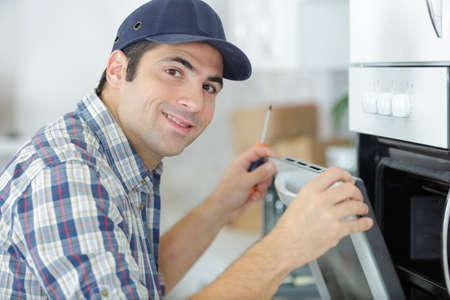 man repairing domestic oven in kitchen