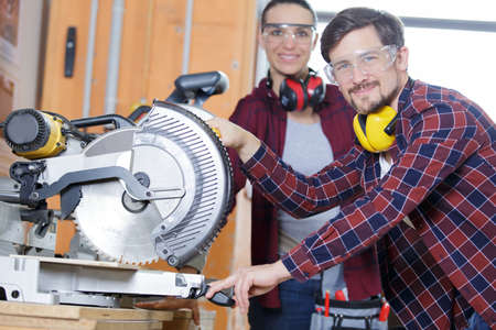 craftsman and woman with safety glasses sawing wood