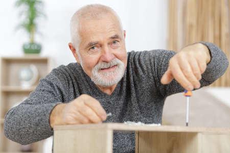 a mature man making furniture