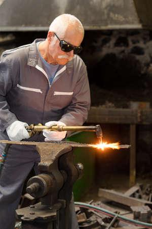 senior blacksmith working in workshop