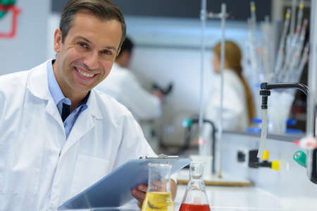 thoughtful technician in lab coat with clipboard
