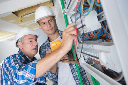tradesmen installing a distribution board