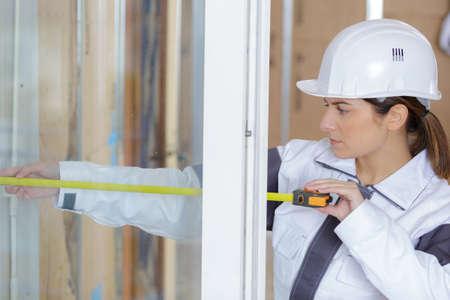 female construction installing window i Foto de archivo