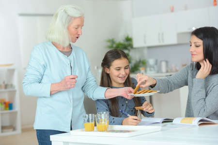 three generations women eating in the kitchen