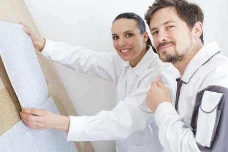 man and woman choosing wallpapers in their new apartment