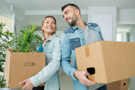 couple moving into a new house carrying cardboard boxes Banque d'images