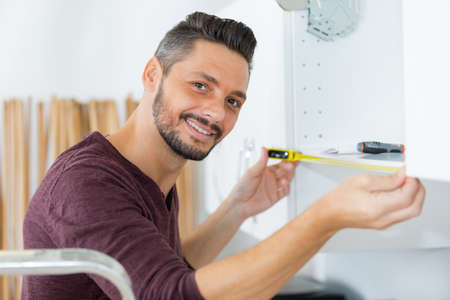 man smiling while measuring the cupboard
