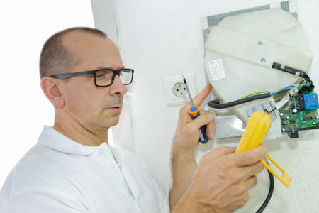 electrician measuring voltage in fuse board