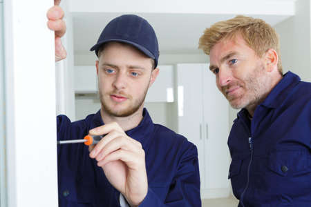 apprentice tradesman using scredriver supervisor watching