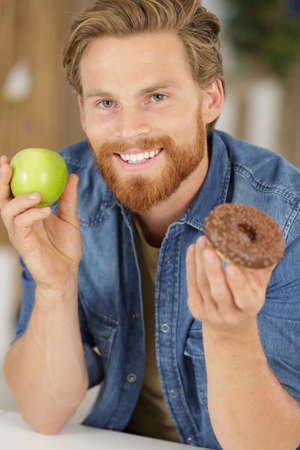 man holding doughnut and green apple