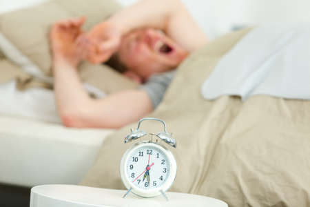young man lying in bed yawning near alarm clock