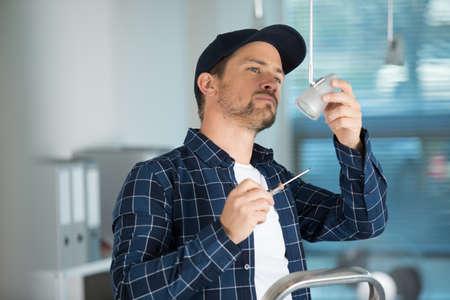 man fixing light at home