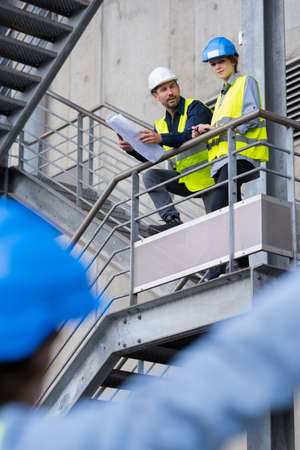 workers on elevated stairway talking to colleague on the ground