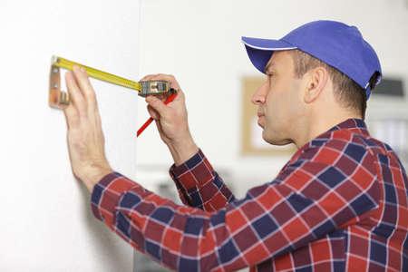 a carpenter measuring a wall