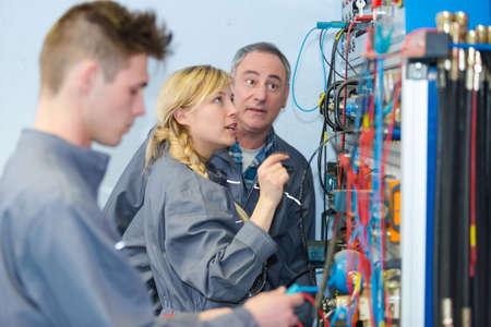 enseignant observant les élèves travaillant sur des circuits électriques Banque d'images