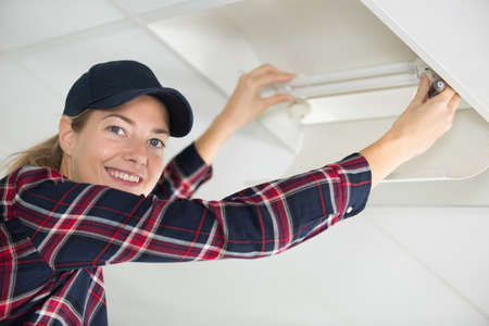 a woman changing light bulb