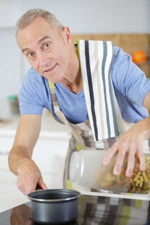mature man cooking and boiling pasta