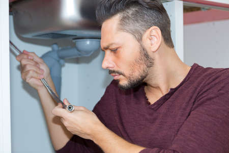 handsome young plumber repairing sink pipe Stockfoto