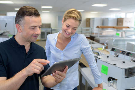 businesswoman with male colleague using digital tablet in office