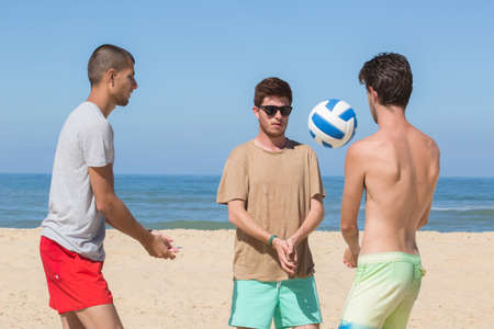 group of friends playing beach volley
