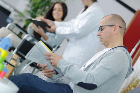 man reading magazine in medical waiting room