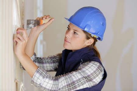 female worker making plaster repair