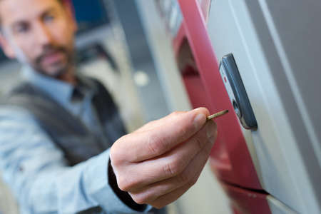 close up of man inserting coin into vending machine Archivio Fotografico