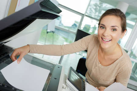 smiling woman makes photocopies in office