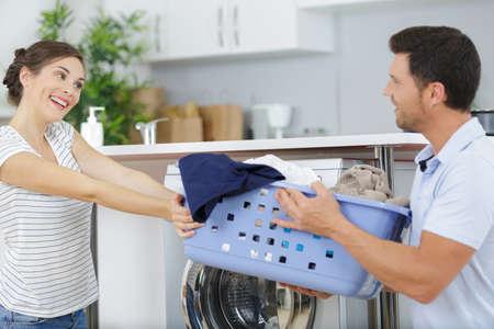 jeune couple partageant les tâches ménagères et faisant la lessive ensemble