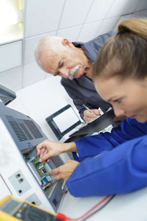 female apprentice fixing a printer Stock Photo