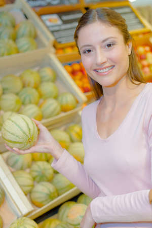 A woman is smiling with a melon