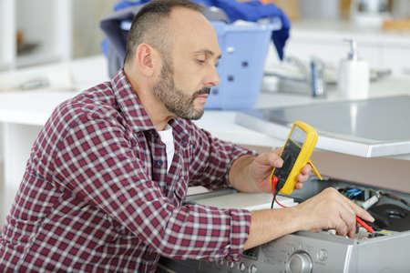 electrician measuring voltage in distribution board closeup