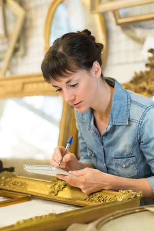 Female artisan working on the decoration of wooden frame