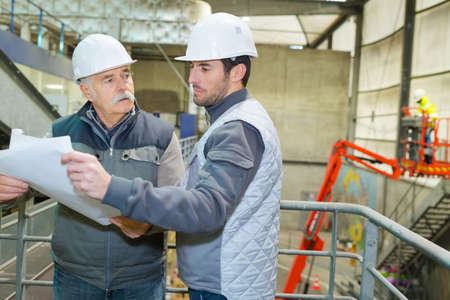 Builder with blueprint shaking partner hand Stockfoto