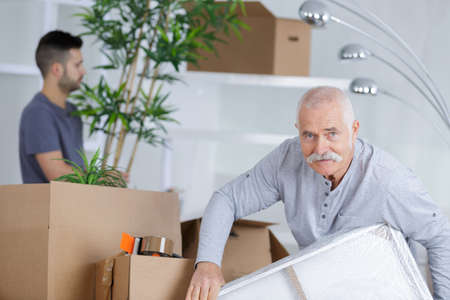 Senior man in empty room with packed moving boxes