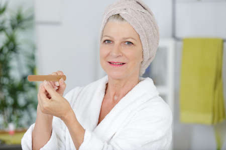 older senior woman doing her manicure Stock Photo