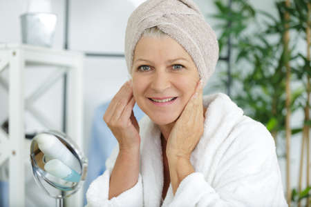 Portrait of senior woman applying anti-aging cream