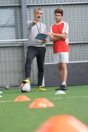 Football coach giving training to player