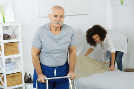 Senior using a zimmer while carer in making the bed