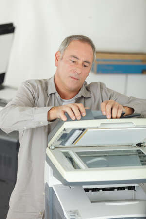 Businessman put printed documents from office printer