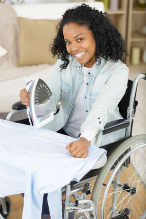 woman on a wheelchair ironing